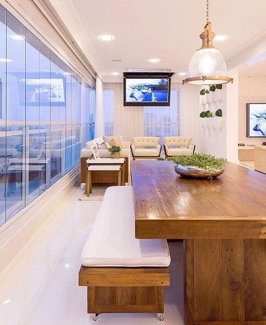 Foto de varanda gourmet espaçosa e clara com uma mesa da jantar grande e sofás ao fundo próximos a um televisor instalado no teto.
