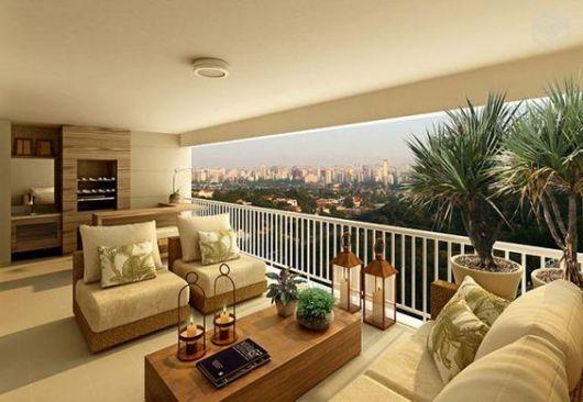 Foto de varanda gourmet espaçosa em um apartamento alto com vista privilegiada para a cidade decorada com poltronas, sofás e uma mesa de centro, além de plantas em vasos.