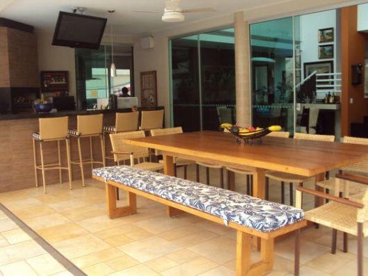 Foto de varanda gourmet espaçosa decorada com móveis de madeira como uma mesa de jantar, bancos e uma bancada ao fundo.