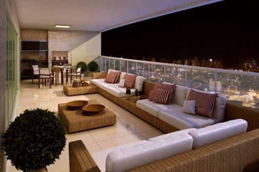 Foto de varanda gourmet espaçosa decorada com sofás espaçosos, plantas e uma pequena mesa de centro.