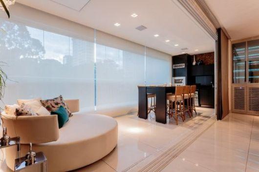 Foto de varanda gourmet espaçosa com um sofá redondo em primeiro plano e uma mesa de jantar ao fundo.