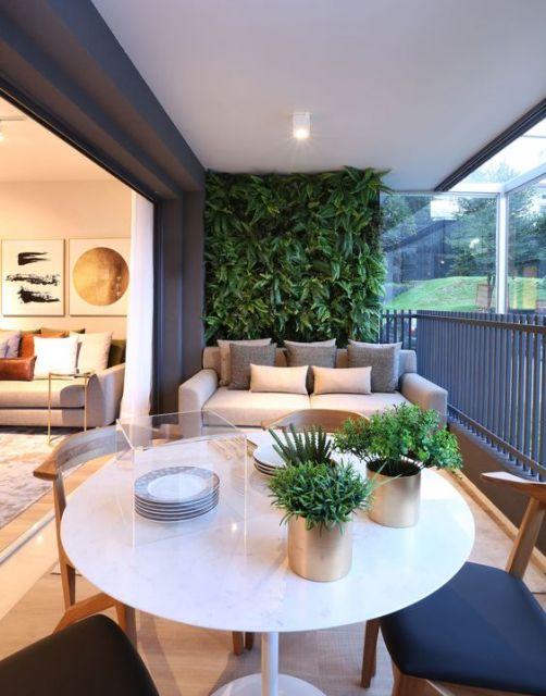 Foto de uma varanda gourmet decorada com uma mesa redonda, cadeira e um sofá com um jardim vertical atrás dele.