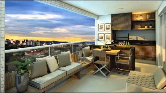 Varanda gourmet grande de apartamento decorada com mesa de jantar, cadeiras e sofá com uma bela vista da cidade durante o crepúsculo.