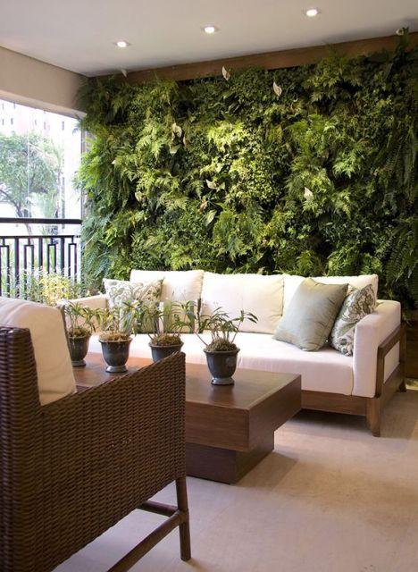 Foto de uma varanda gourmet com sofás e mesa de centro e um jardim vertical bem cheio atrás do sofá.