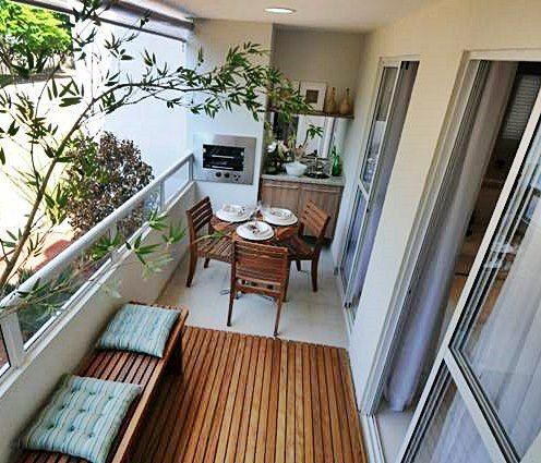 Foto de uma varanda gourmet vista de cima com chão  e móveis de madeira e plantas do jardim externo adentrando ela.