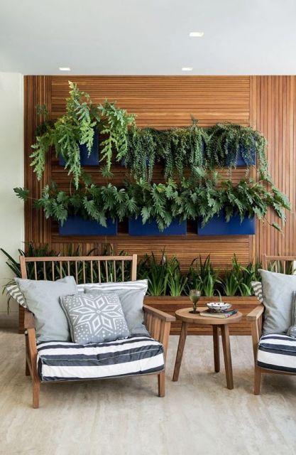 Foto de uma varanda gourmet com duas poltronas e uma parede de madeira ao fundo que comporta um jardim vasos com plantas.