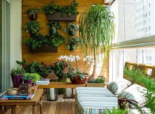 Foto de uma varanda gourmet decorada com muitas plantas, tanto nas parede quanto em vasos no chão.