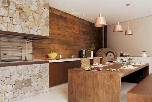 Foto de uma varanda gourmet com a churrasqueira feita de pedras e o resto do ambiente construído com madeira, como a mesa de jantar e a parede.