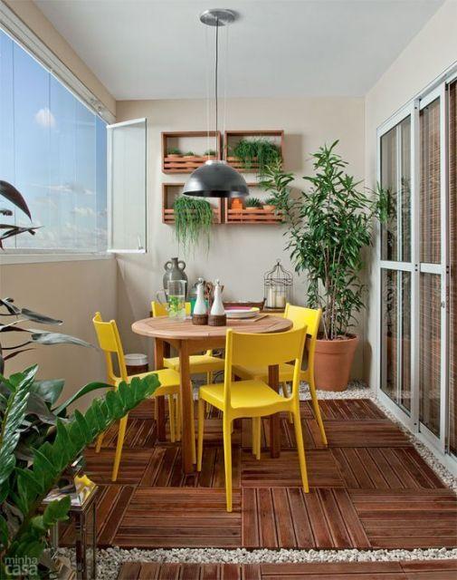 Foto de uma varanda gourmet com cadeiras coloridas, chão de madeira e vasos de plantas dispostos pelo ambiente.