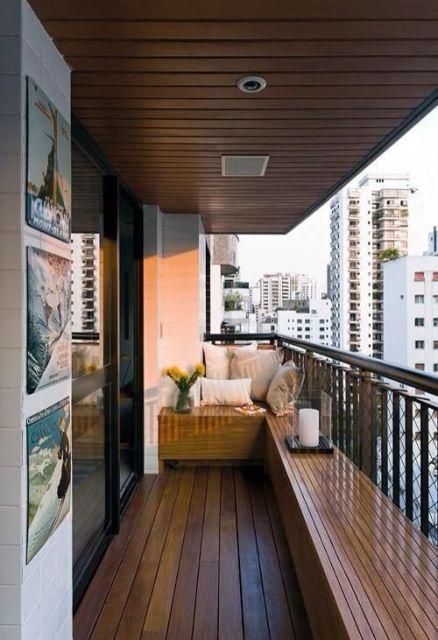 Foto de uma varanda gourmet com o teto e chão feitos em madeira e um banco lateral com o mesmo material.