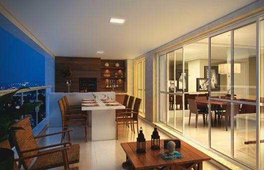 Varanda gourmet de apartamento decorada com cadeiras, mesa de jantar e mesa de centro.