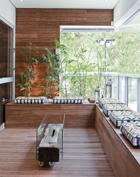 Foto de uma varanda gourmet construída com o chão, o banco e a parede em madeira.