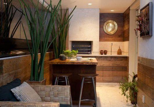 Foto de uma varanda gourmet decorada com móveis de madeira como a banca e a mesa central.