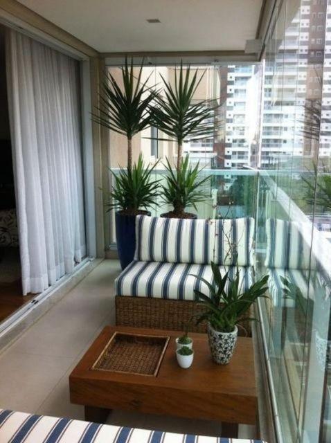 Foto de uma varanda gourmet pequena decorada com vasos de plantas, uma poltrona listrada e uma mesa de centro.