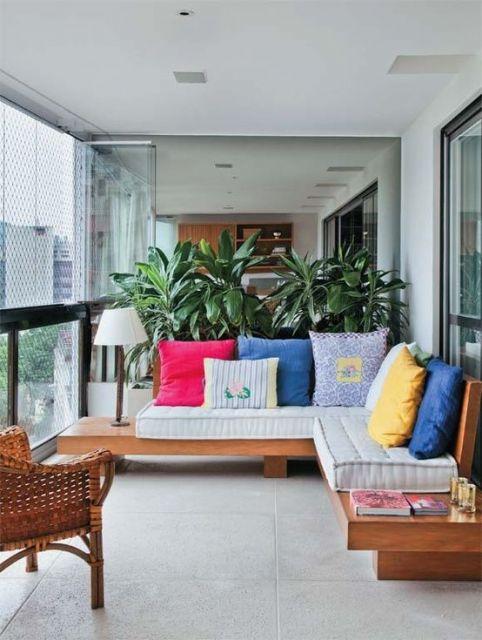 Foto de uma varanda gourmet pequena com um pequeno sofá e plantas posicionadas atrás dele.