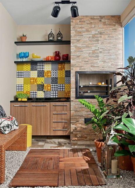 Foto de uma varanda gourmet pequena com um pequeno armário ao lado de uma churrasqueira, piso de madeira, plantas e parte da parede decorada com porcelana,