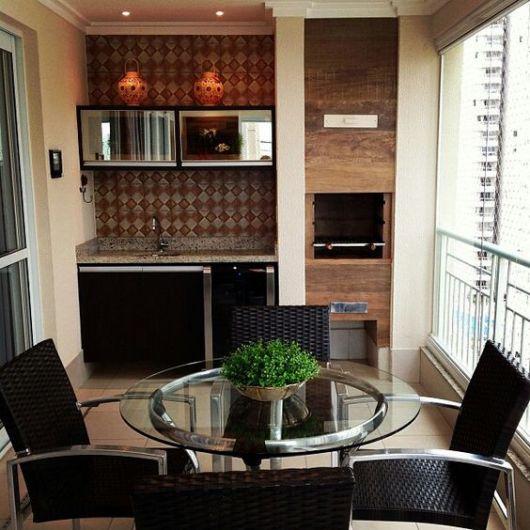 Foto de uma varanda gourmet pequena com um armário de parede ao lado de uma pequena churrasqueira e uma mesa redonda rodeada por quatro cadeiras.