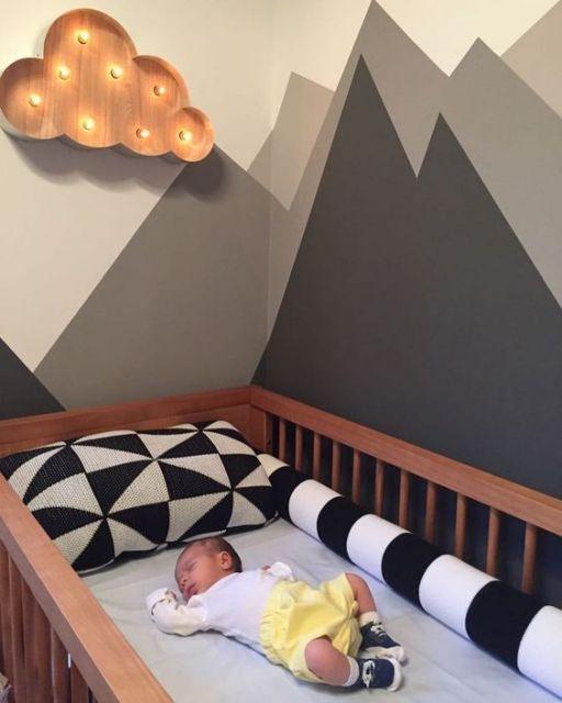 Quarto de bebê com berço de madeira e paredes em branco e cinza.