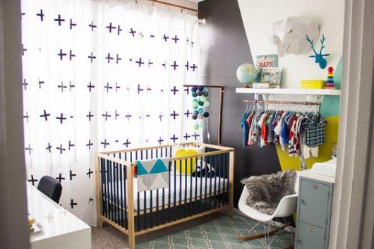 Quarto com roupas do bebê expostas em cabides.