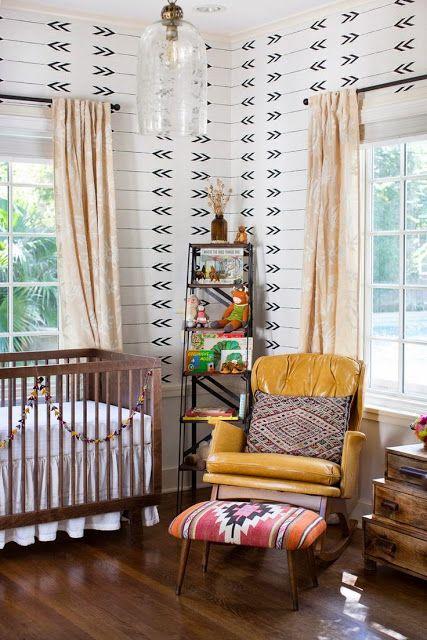 Quarto de bebê vintage com berço de madeira e poltrona amarela.