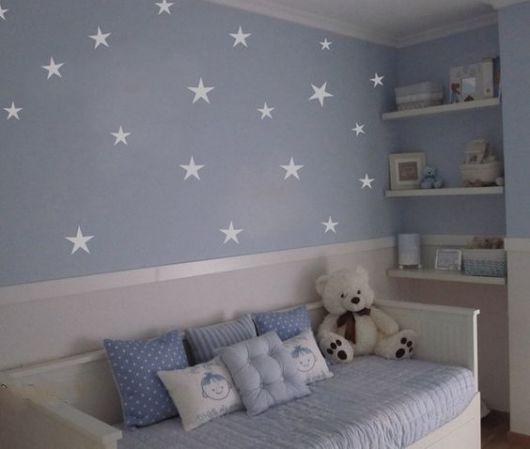 Quarto de bebê com parede azul com estrelas.