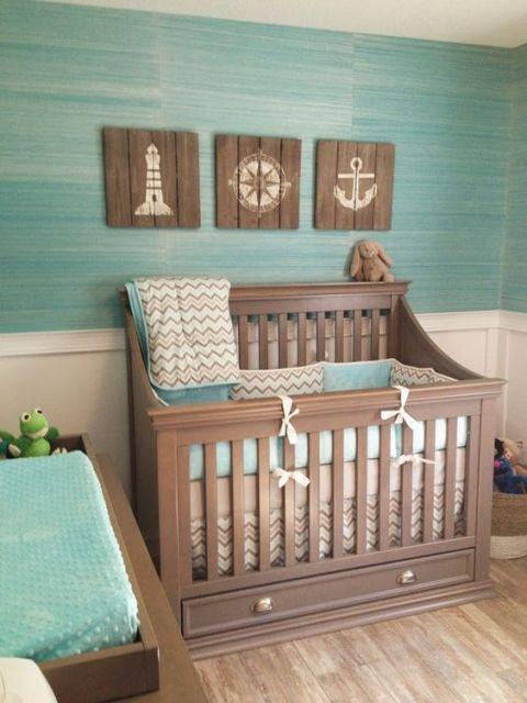 Quarto com parede verde e quadros com desenhos de farol, âncora e timão.