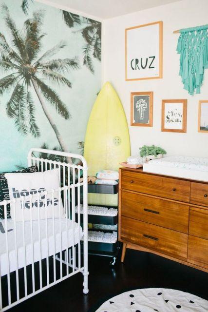 Decoração de quarto de bebê praiana, com prancha de surf e parede com imagem de coqueiros.