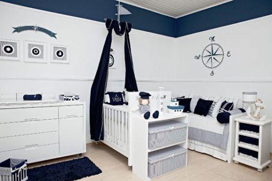 Quarto branco e azul com desenhos referentes a navios nas paredes.