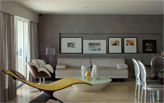 Sala cinza decorada com quadros, sofá branco branco, poltronas, mesa de centro redonda e divã amarelo moderno.