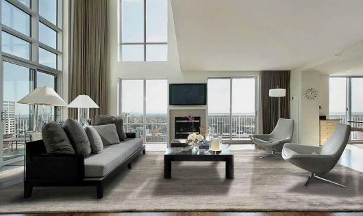 Modelo de sala clean com janelas grandes e sofá cinza.