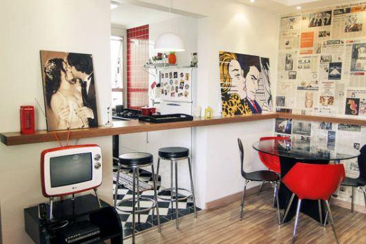 Modelo de cozinha junto de sala de estar nas cores branco, vermelho e preto.