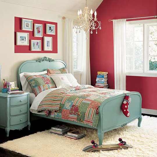 Quarto com parede vermelha, mural na mesma cor e cama vintage com cômoda no mesmo estilo na cor azul.