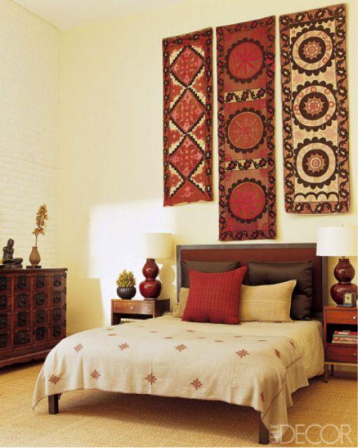 Quarto com decoração amarelo claro nas paredes, tapetes indianos enfeitam a parede acima da cabeceira da cama e a cama combina com toda decoração do quarto indiano.