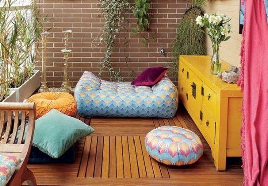 LOcal de meditação com piso de madeira e móvel amarelo, com almofadas coloridas no chão.