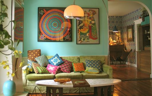 Sala na cor azul turquesa, com sofá verde e almofadas coloridas.