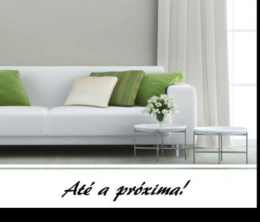sofá branco com almofadas na cor verde e branco.