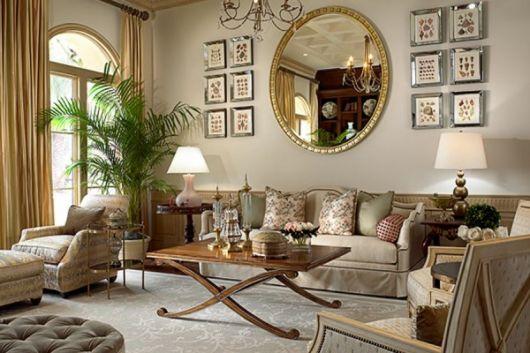 Sala com parede clean com quadros pequenos espelho redondo com moldura dourada, sofá grande com almofadas, mesa de centro em madeira.