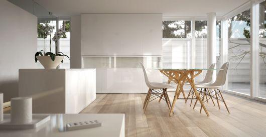 Cozinha branca com mesas e balcão de madeira na mesma cor, em estilo minimalista.