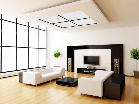 Sala ampla em tons de branco e marrom com piso de madeira.