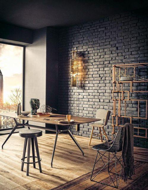 Sala de jantar com mesa de madeira e matal, paredes tijolo a vista cinza e cadeiras estilo banquetas.
