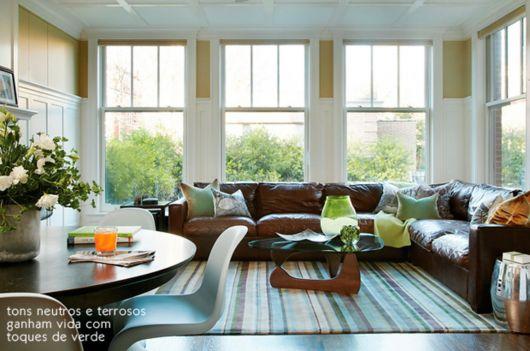 Sala iluminada com sofá marrom grande e fofo, janelas grandes e mesa de centro de madeira.
