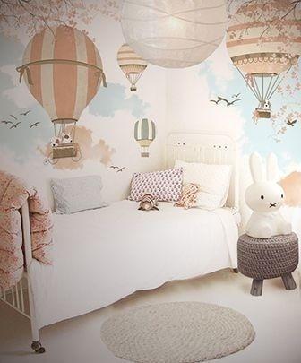 Quarto com papel de parede de balões e camada com edredom branco.