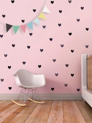 Papel de parede rosa com corações pretos.