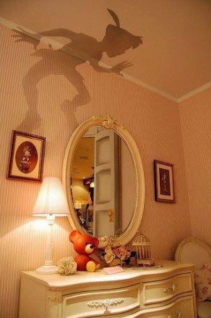 Quarto com espelho, quadros e papel de parede que imita a sombra do Peter Pan.