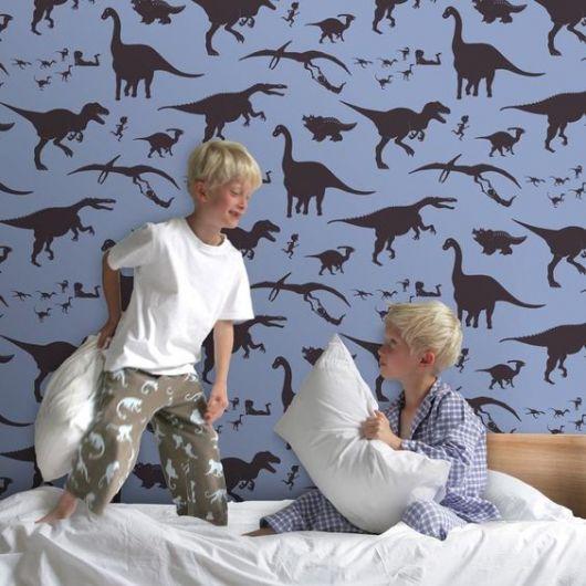 Dois meninos em frente a parede com papel de parede azul com dinossauros.