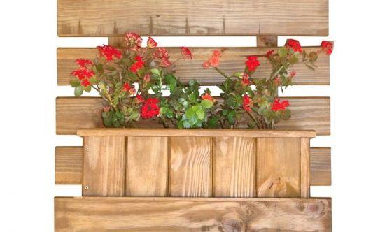 Vaso de madeira crua claro com flores vermelhas plantadas, para pendurar na parede.