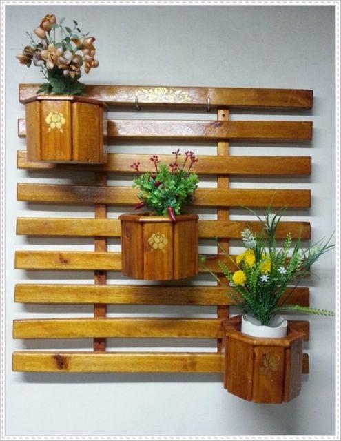 Modelo de madeira marrom para parede com tres vasos pequenos.