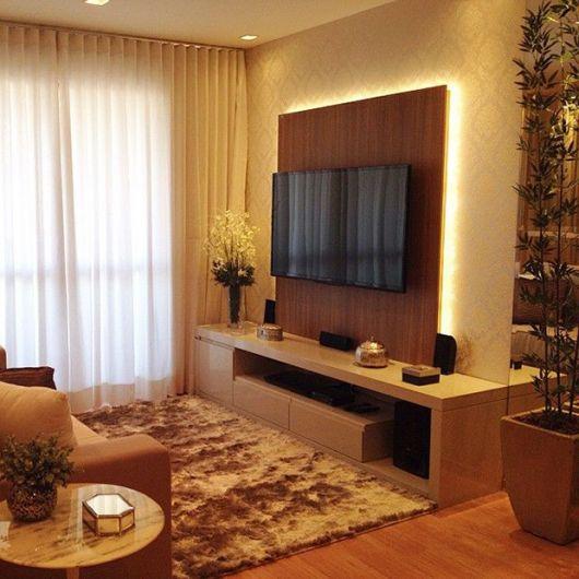 Modelo de sofá simples na cor marrom em sala clean na cor amarela e tapete felpudo.