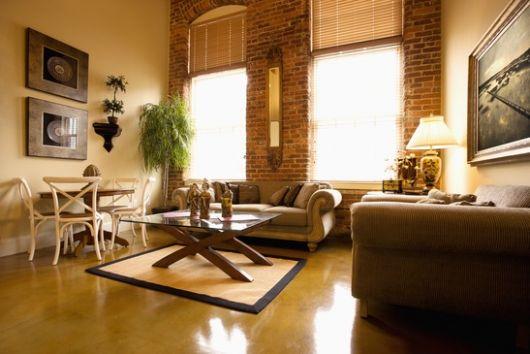 Modelo de sala moderna com piso porcelanato, mesa em madeira na cor nude com sofá marrom.