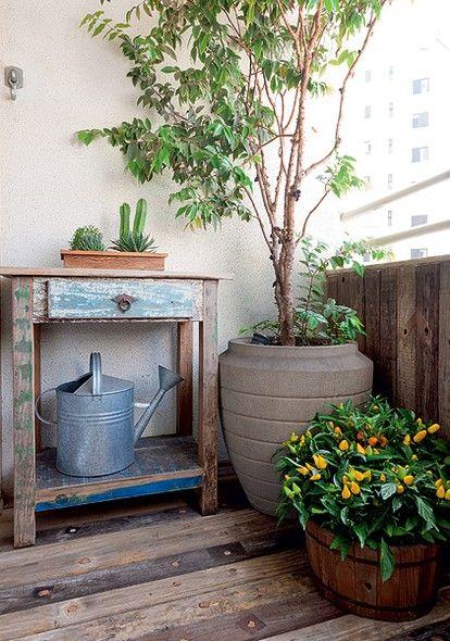 Varanda com paredes brancas e móvel antigo com decorado em vasos de flores.